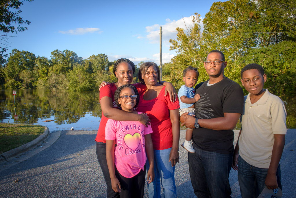 Tharon Gillispie's family stands beside the flood-swollen Tar River in Greenville, N.C. They evacuated their home in nearby Grifton as the water rose. Standing, left to right, Tharon's wife Cynethia, daughter Emaya, 11, mother-in-law Cherie Perkins, Tharon holding baby Logan, and son Zeke, 12. ©2016 World Vision, Laura Reinhardt)