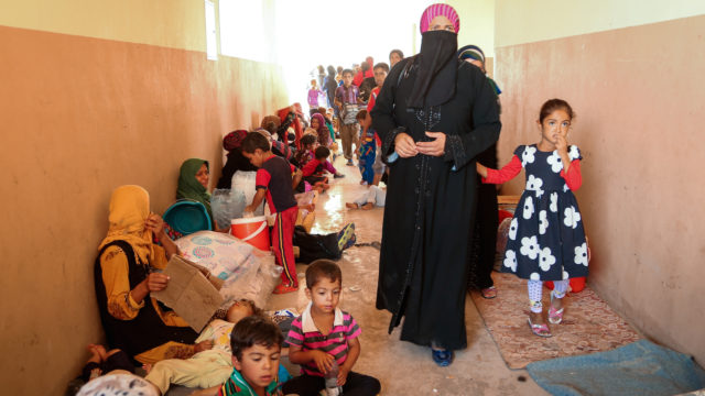 Iraq crisis: Hada and her daughter walk through the hall of a former school that serves as a transition center for women and children at Debaga camp in Iraq. (©2016 World Vision, Suzy Sainovski)