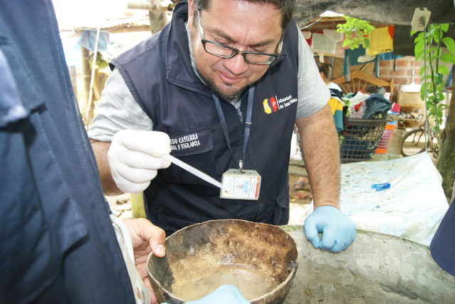In an effort to battle the Zika virus, an Ecuadorian health official treats water to prevent mosquitos from laying eggs in a container. (©2016 World Vision, Julia Carrion)