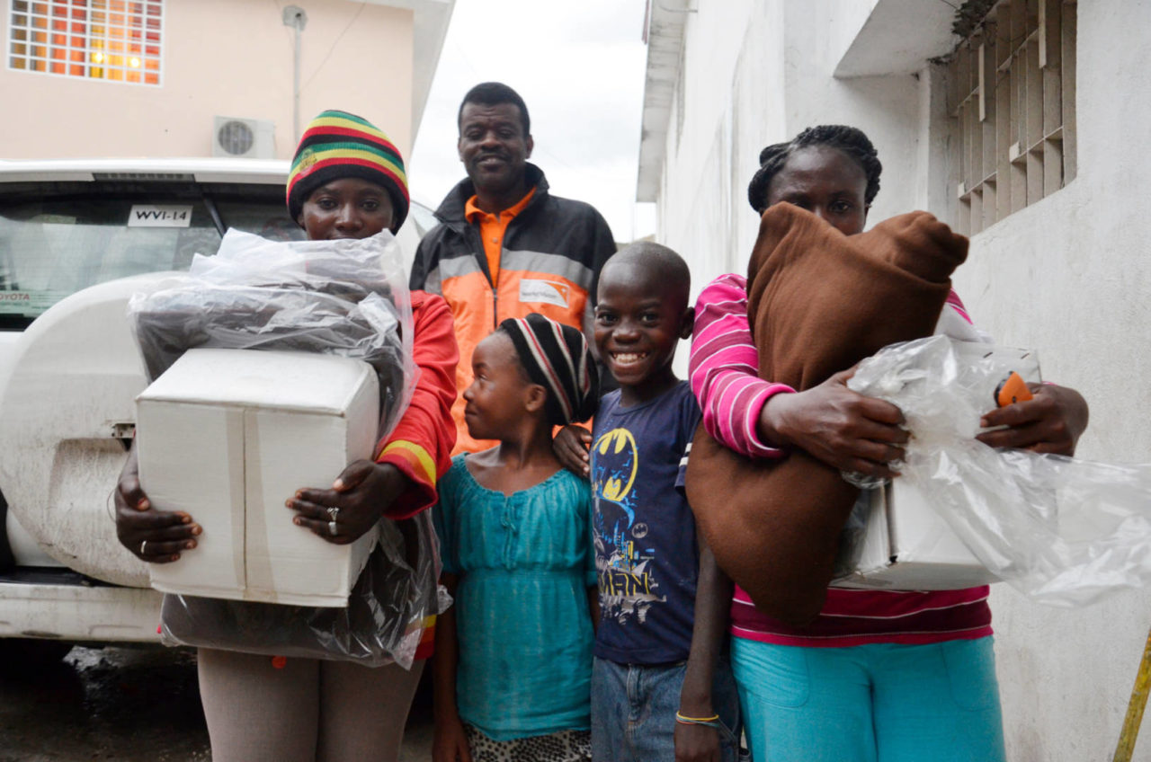 Two displaced moms and their children receive blankets and hygiene kits at Agape Church in Haiti. Lesly Michaud, World Vision response manager, (center) and staff distributed water and relief supplies in Port-au-Prince after Hurricane Matthew. (©2016 World Vision, Claudia Martinez)